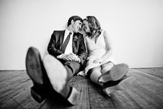 gorgeous black and white photo of the the happy couple sitting on the floor - fun perspective - photo by Seattle based wedding photographer Sean Flanigan