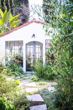 This is the back side of a garage,converted with new doors & windows as a pool house & with a beautiful garden