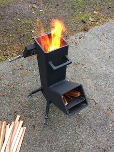 """Small rocket stove built out of scrap 5"""" sq tubing and other bits and pieces. Adjustable legs, clean out door and cooking grate."""