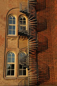 A spiral staircase, Gothic windows and an old brick wall.