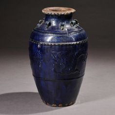 Large Martaban Jar, China, the ovoid body rising to a narrow neck and a flared scalloped rim, the body decorated with two raised horizontal bands, one incised with diagonal lines, the sides of the jar decorated with dragons chasing a flaming pearl in relief, with eight looped handles at the shoulders and decorated with a deep blue glaze, ht. 19 3/4 in.