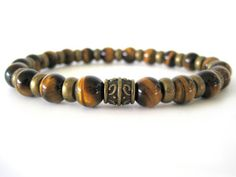 Handsome men's beaded stretch bracelet with 8mm Tiger Eye beads and antiqued brass accent beads.The Tiger Eye beads have deep dark brown tones highlighted with stunning golden-yellow streaks making this quite the masculine bracelet!