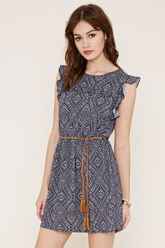 This woven dress flaunts an abstract print with ruffled cap sleeves, a ruffled detail across the chest, and a removable braided faux suede belt with tassel ends.