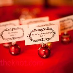 escort cards printed with an antique border and held up with a tiny Christmas ornament