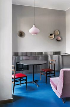 The apartment of Carlo Prada in Milan, Italy featured in Living Corriere della Sera: Leggera chairs by Gio Ponti (1951), sofa settee by Marco Zanuso (c.1960s), glass pendant light by Massimo Vignelli by Venini (c.1960s) and ceramic plates on the wall...