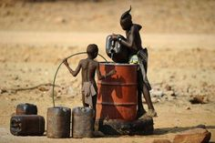 Two Himba boys pour water into a tank in 2010 in the village of Okapare, near Opuwo in northern Namibia.