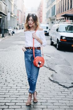 A white off-the-shoulder top with boyfriend jeans and fringe sandals