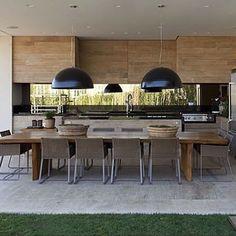 WEBSTA @ ohlaemcasablog - Varanda gourmet em uma combinação certeira  Bancadas e pendentes na cor preta realçam os armários e a mesa em madeira ☝️ Para trazer a leveza necessária, a arquiteta apostou em um espelho acima da rodabanca para refletir o belo jardim ao fundo  | Por Débora Aguiar #gourmetohlaemcasa
