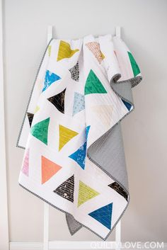 Triangle Pop Quilt Pattern by Emily of quiltylove.com. A modern triangle quilt pattern. Triangle Pop is a fat quarter friendly quilt. This quilt pattern is designed for the intermediate quilter. It uses traditional piecing and a 60 degree triangle ruler is recommended but a template is provided. Includes instructions to make baby, throw, twin and queen size quilts. #modernquilts #fatquarterquilt #quiltpattern Quilting Projects, Quilting Designs, Quilting Ideas, Sewing Projects, Sewing Ideas, Sewing Patterns, Triangle Quilt Pattern, Triangle Quilts, Quilt Ladder