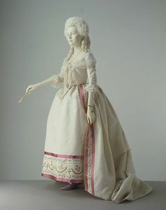 Dress | c. 1780-85  This gown demonstrates the fashionable styles in women's formal dress of the 1780s. The hoop has changed from the square shape of earlier decades to a round profile. A stomacher is no longer needed, because the gown now meets in the front. The cream silk is adorned only at the edges with an embroidered band, ribbon and a stencilled fringe. This restraint in decoration illustrates the growing influence of the Neo-classical style in textile design.  I LOVE the pink accents!!!