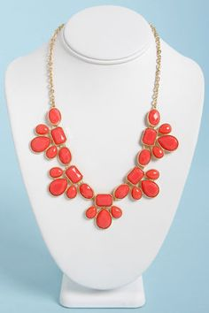"""Teach your peers a thing or two about accessorizing with the glamorous Gem Class Coral Statement Necklace! Smooth and faceted coral enamel gems mingle together in golden settings as they dangle in clusters from a golden chain. Charms dangle 1.5"""" from center. Necklace measures 17.5"""" around, plus a 3"""" extender chain. Lobster clasp closure. Man made materials. Imported."""