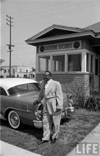 """Dootone Records president Walter """"Dootsie"""" Williams stands in front of the building that houses his label at 9514 South Central Avenue, Los Angeles. From approximately 1920 to 1955, Central Avenue was the heart of the African-American community in Los Angeles, with active Rhythm and Blues and Jazz music scenes. Local luminaries included Eric Dolphy, Art Pepper, Chico Hamilton, and Charles Mingus. Other jazz and R&B musicians associated with Central Avenue in LA include Benny Carter,..."""