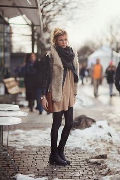Clara in furry vest, beige sweater, leather motorcycle jacket, and pleather leggings.