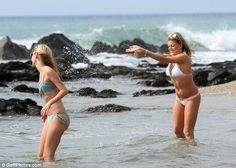 Summer fun: The pair played about in the ocean splashing each other with water to cool down in the summer sun