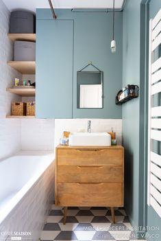Cette petite salle de bains accueille une baignoire et de nombreux rangements