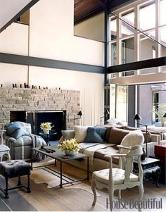 In this living room of a Pennsylvania house, designed by Jeffrey Bilhuber, one side of a back-to-back sofa faces the room, and the other side looks out through folding glass doors toward the swimming pool. The club chair has ivory-and-gray strapwork that echoes the crossbeams of the architecture.   - HouseBeautiful.com