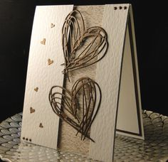 Mary Ann & Kevan anniversary card 2016 Tim Holtz heart dies cut in a Bronze metallic paper. Tiny hearts are Memory Box. Inset paper is from Pinterest. IRL it has kind of a 3D look with hearts here and there. Faux dots made with a circle punch and stylus. Hammered card stock panels are popped with fun foam. Inside it simply says Happy Anniversary (embossed) with a small heart accent. Made by Peggy Dollar