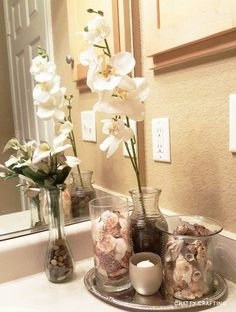 A beach themed bathroom idea on a tight budget. I think this would be great as apartment/small bathroom decor if you're not into nautical themes, but if your more of a coastal decorator like me. I like this spa-like vibe. Dollar tree silver tray, seashell vase fillers, river rocks... #dollartree #decor