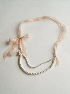 I'm totally gonna steal this idea because I have this short pearl necklace that I can totally extend into a longer necklace with ribbon as shown here