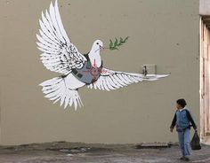 A Palestinian boy looks at one of six new images painted by British street artist Banksy as part of a Christmas exhibition in the West Bank town of Bethlehem