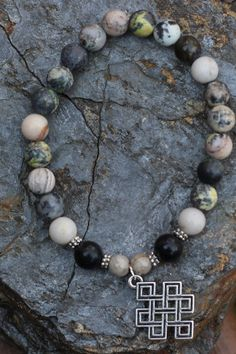 What you see is what you get - this is the only one of this bracelet I will make! Get it before its gone! - Silver tone Eternal Knot charm. - Various natural stone beads including: serpentine, black jasper, and feldspar. - 7 Inches un-stretched (approximately). This bracelet best fits people with a medium or large frame. - Ships from Canada.  The Endless Knot, also called the Tibetan Knot or Chinese Knot, has no beginning or end. The multiple semi-precious stones guarantee this bracelet…