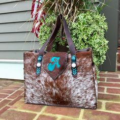 The Buckaroo Diaper Tote with Indianhead and buffalo nickel conchos on the straps, exterior side pockets lined in suede and a big, fun turquoise A on the flap. Custom purses and totes from gowestdesigns.us