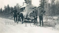 FMP.87.25.54    Circa 1920  Mounties (police officers) changing a tire of a Studebaker convertible by the side of the road.