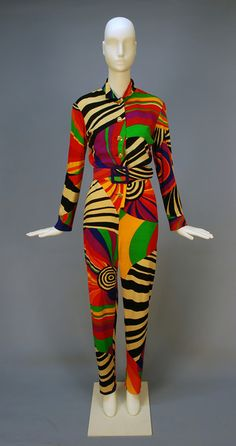 "LEONARD, PARIS, PRINTED WOOL ""PASTIS"" JUMPSUIT, c. 1970. Long sleeve with stand collar in vibrant swirling abstract signature ""Leonard"" print, brass buttons and wide self belt."