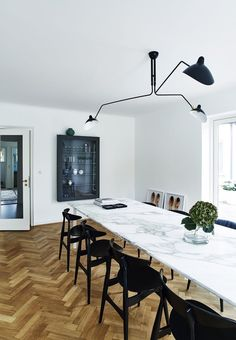 Dining room with a long marble table surrounded by black dining chairs by Hans J. Wegner. We love the herringbone parquet flooring.