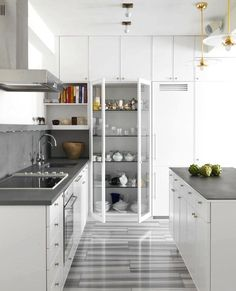 Annabelle Selldorf Kitchen/ grey and white stone floor, glass front pantry cabinet