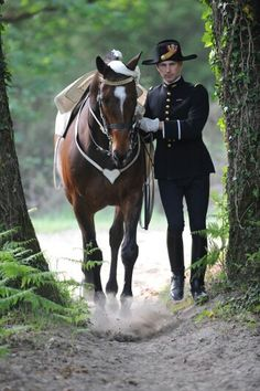 Horse in its tack and rider in his black uniform tippacle of cadre noir de saumur