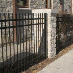 Photo of a custom residential masonry pillars installed between an iron fence. Designed and installed by First Fence Company in Hillside, IL.