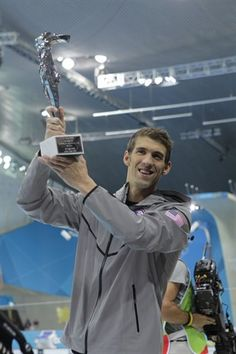 The U.S.'s Michael Phelps smiles as he holds up his award recognizing him as the most decorated Olympian.