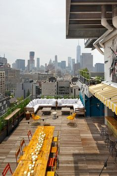 The gritty New York skyline creates an amazing backdrop for the orange and yellow chairs, wooden deck and colourful yellow and white striped awning at Azul Rooftop Bar on top of Hotel Hugo in Greenwich Street, New York