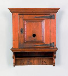 """Rare Pennsylvania walnut hanging cupboard, ca. 1750, with a molded cornice above a raised panel door with a bull's-eye glass opening and bold wrought iron hinges, above scalloped sides and a lower shelf, 33"""" h., 23"""" w. This is one of the finest Pennsylvania hanging cupboards extant. Collection of H. Richard Dietrich."""
