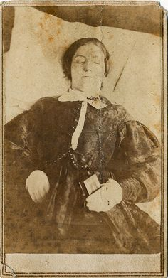 Said to be an army hospital nurse, this post mortem (death portrait) photograph shows a young woman holding a book, possibly a small bible or testament. The revenue stamp on the back dates this image to 1864. Annapolis was the site of one of the largest Union Army Hospitals during the Civil War and at least 5 female nurses died of diseases caught while tending patients there. Three of them died in late 1863 and two died in early 1865. The 1864 stamp on this image places it between those two…