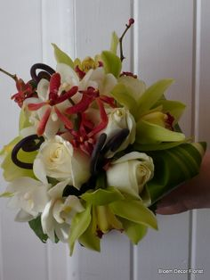 Bridesmaid's bouquet with white roses, green cymbidium orchids, white cymbidium orchids, red oncidium orchids, monkey tail and variegated aspidistra leaves.