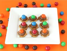 Just melt Hershey's kisses onto tiny twist pretzels (275 degrees, 3 minutes), remove, and immediately press a single m&m; on each. Refrigerate until eating to make sure they are deliciously solid!