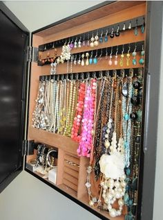 Jewelry hangers behind picture frame/mirror