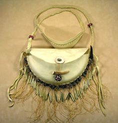This is the first and only bag/purse I have ever made. It is deer rawhide and deerhide leather for the strap. The antler pieces are also deer. It was made in a way that would have been possible 100's of years ago. The glass beads are lampwork which I made in the esthetic of vintage red white heart beads.