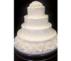 Add an untraditional texture or pattern to your traditional white wedding cake for a little unexpected twist. Garnished with white sugared roses.