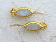 Inspired by the intriguing beauty of ethnic jewels, these handcrafted earrings have a simplicity and sophistication which allows for true versatility whether pairing with business wear, evening attire, or dressing up your casual look.  With the white Moonstone, each earring is wonderfully balanced with 24k solid gold bezel with hammered 24k solid gold dots decorating each stone.  For practicality and elegance, the hooks are handmade locking French wires made of 14k yellow gold with 9k gold…