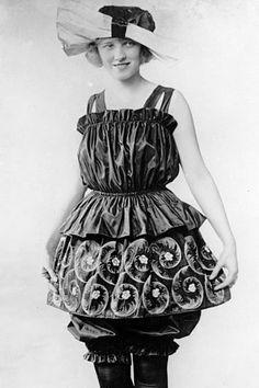 1905. Junge Frau in steif aussehender gerüschter Kleidung, Rock über gerüschten Hosen und mit großem Hut.; Rechte: AKG