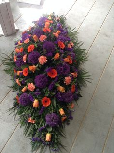 Funeral Flowers. Cadbury purple and Terry's orange funeral coffin spray www.thefloralartstudio.co.uk