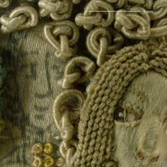 The under drawing on the satin foundation fabric over which the looking glass is held reveals a face with a distinctly different expression from that in the mirror. Knots of silk purl are couched in place. Magnification 10x. Image by Cristina Balloffet Carr. Embroidered mirror frame, 1672. British. Silk, metal, glass beads, mica, seed pearls. 28 3/4 x 23 3/4 in. The Metropolitan Museum of Art, New York. Purchase, Mrs. Thomas J. Watson Gift, 1939 (39.13.2a)