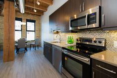 The PACIFIC at District Condos - Loft style conversion condos featuring exposed brick, century old wood beams, 14 ft ceilings and modern finishes.