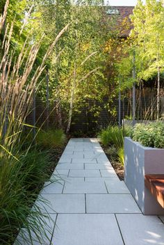 External Concepts used Beola Bianca Porcelain paving in this exotic garden design, complimenting the colouring of the planters and creating contract between the greenery.