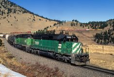 https://flic.kr/p/23SZ1MZ | Pushing toward Tunnel 1 | As the head end of westbound BNSF MDENSTO approaches Tunnel 1 in the background, a manned helpers set of two Burlington Northern EMD SD40-2s push hard on the rear of the train that just cleared Blue Mountain Drive grade crossing west of Clay, Colorado, on January 2, 2001. The train is looping over the mouth of Coal Creek Canyon at milepost 23 on former Rio Grande, now Union Pacific's Moffat Tunnel Subdivision.