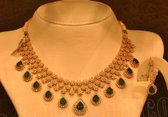 Malabar gold - Beautiful diamond necklace with hanging emerald drops, complemented by matching earrings