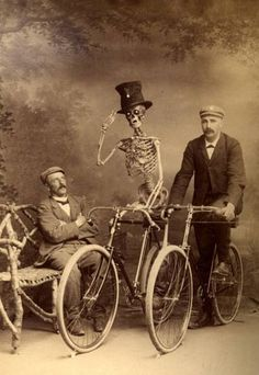 Gentlemen posing for a portrait with their bicycles and a skeleton wearing a top hat.